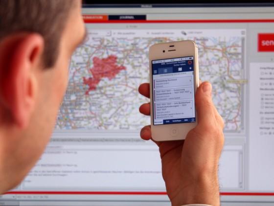 Das Modulare Warnsystem (hinten im Bild) und die App (auf dem Smartphone) zur Warnung der Bevölkerung. /Foto: BBK)